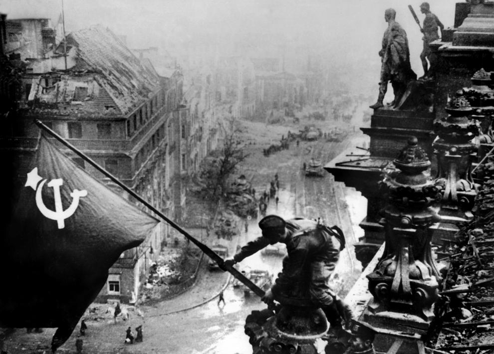O fotografie făcută pe 2 mai 1945 în Berlin arată un soldat sovietic ridicând steagul roşu pe clădirea Reichstag-ului, după ce forţele aliate au pătruns în oraş, încheind astfel cel de-al doilea război mondial.