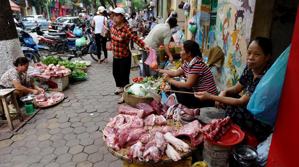 Vânzători comercializează carne de vită şi de porc pe trotuarul unei străzi din centrul oraşului Hanoi, marţi, 24 mai 2011.