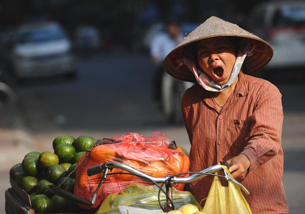 O vânzătoare de legume cască în timp ce se plimbă cu standul său mobil pe o stradă din Hanoi, luni, 24 octombrie 2011.