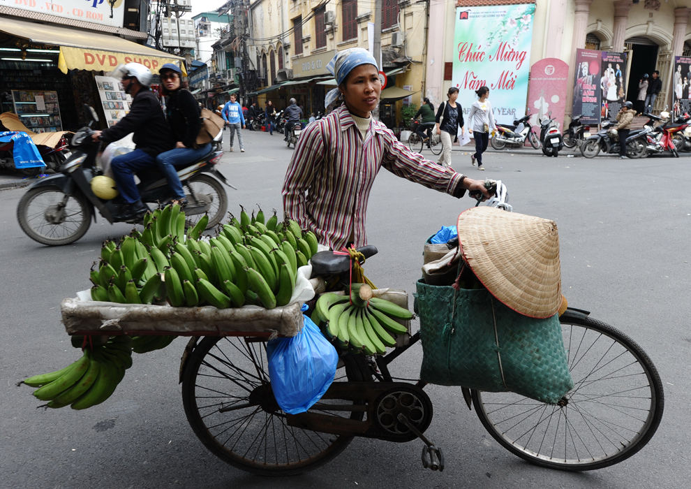 O vânzătoare împinge o bicicletă pe care se află banane de-a lungul unei străzi din Hanoi, înaintea Anului Nou lunar tradiţional denumit Tet, joi, 19 ianuarie 2012.