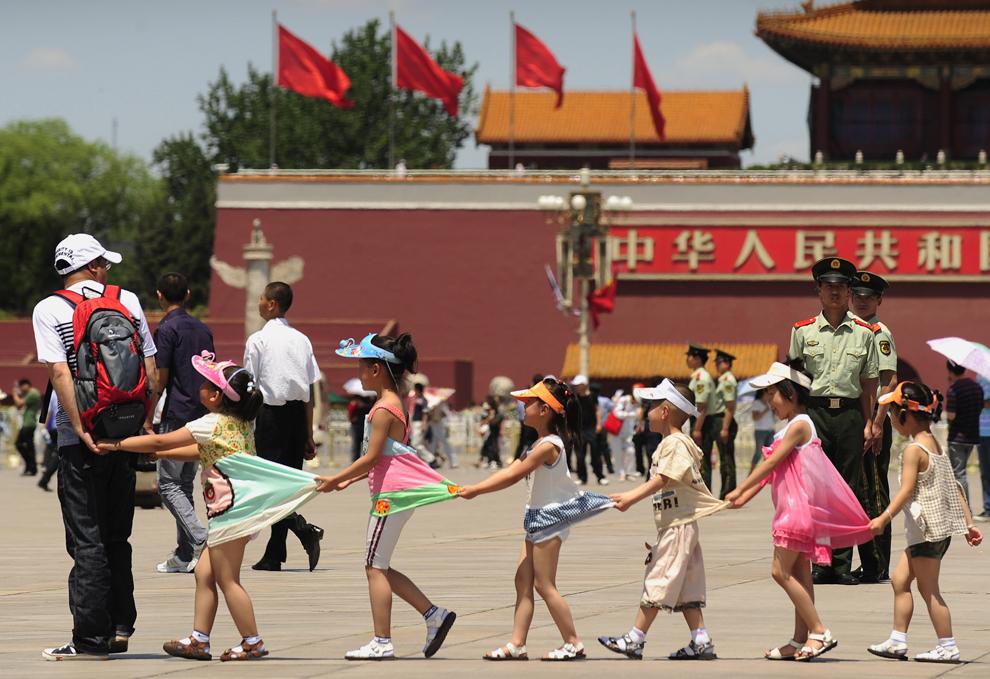 Mai mulţi copii se joacă în timp ce poliţişti chinezi supraveghează Piaţa Tiananmen, în Beijing, miercuri, 3 iunie 2009.