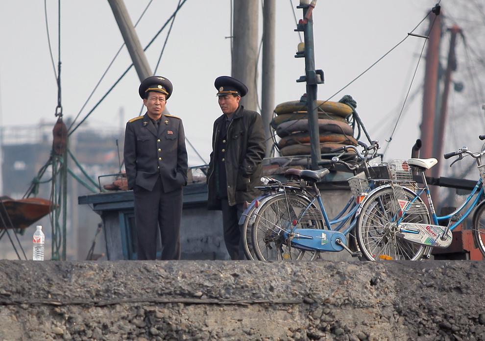 Oficiali nord-coreeni aşteaptă în docurile de pe malul râului Yalu, în oraşul nord-coreean Sinuiju, joi, 4 aprilie 2013.