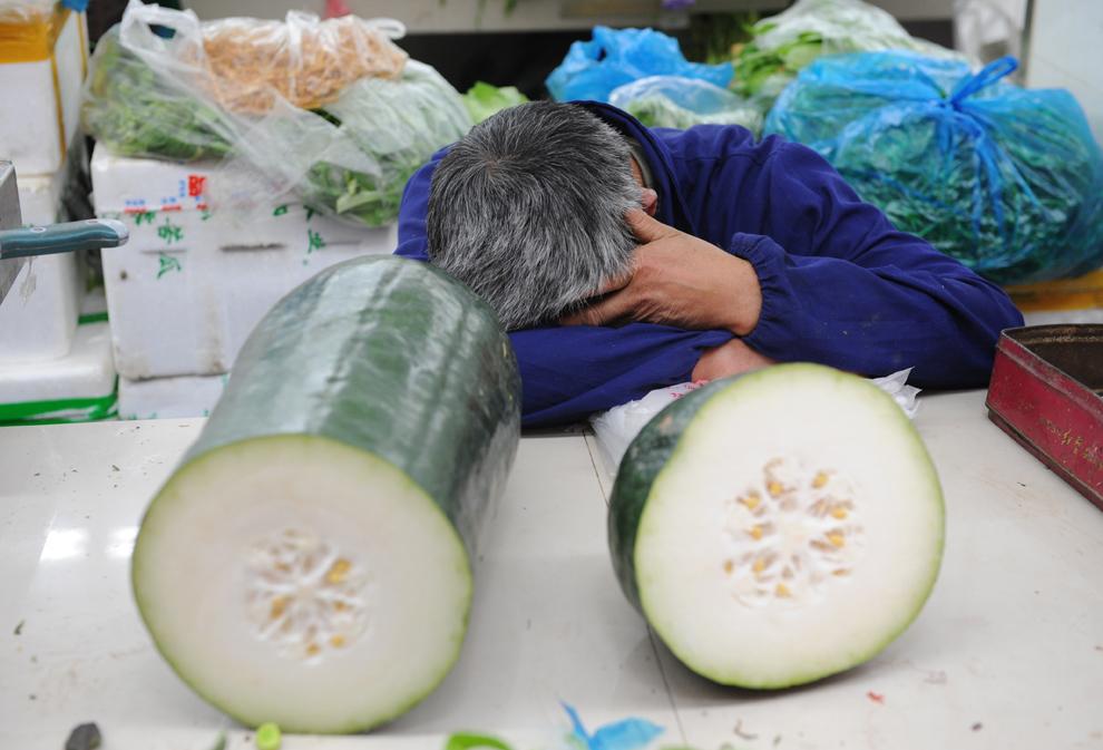 Un vânzător de legume doarme într-o piaţă din Shanghai, luni, 15 aprilie 2013.