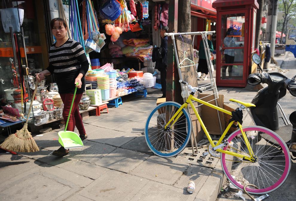 Proprietara unui magazin mătură trotuarul din faţa acestuia, în Shanghai, luni, 15 aprilie 2013.