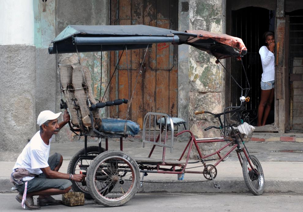 Un bărbat repară o bicicletă folosita ca taxi, în Havana, luni, 2 februarie 2009.