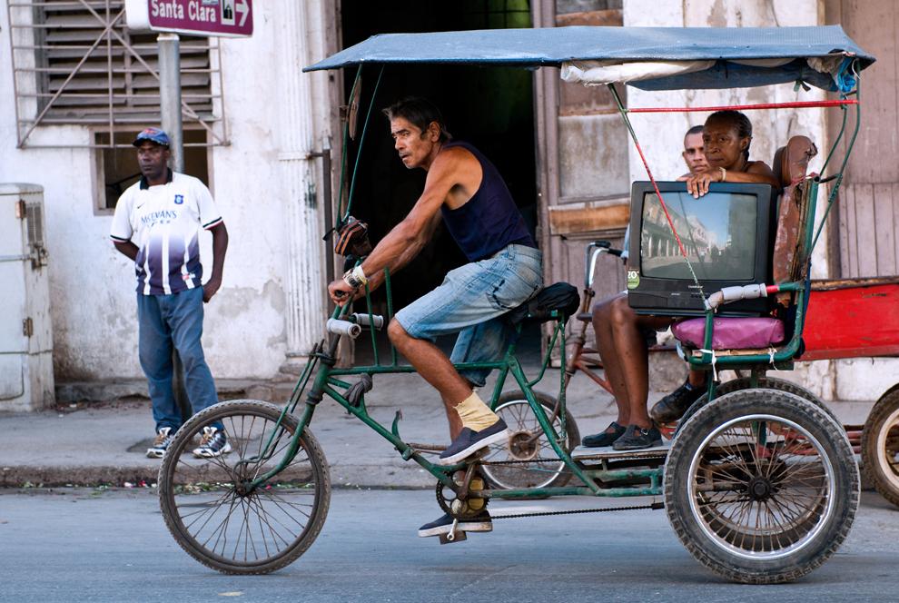 Un cubanez transportă un pasager cu o 'bicicletă taxi', în Havana, marţi, 12 iulie 2011.