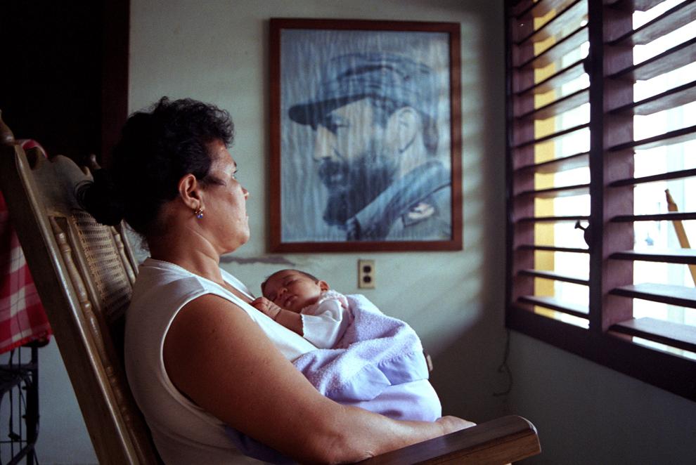 O bunică cubaneză îşi leagănă nepotul în faţa unui portret al liderului cubanez Fidel Castro, în Baracoa, Cuba, marţi, 15 aprilie 2003.