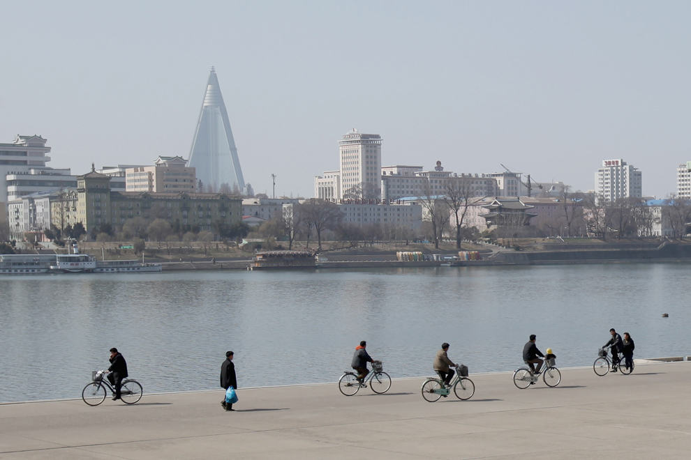 Biciclişti pedalează pe malul rîului Taedong, în Phenian, duminică, 3 aprilie 2011.