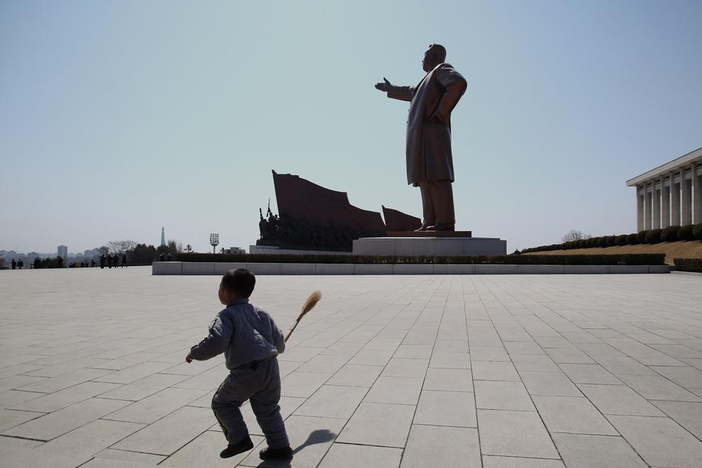 Un copil aleargă în apropierea monumentului Statuii Eterne a lui Kim Il Sung, în Phenian, duminică, 3 aprilie 2011.