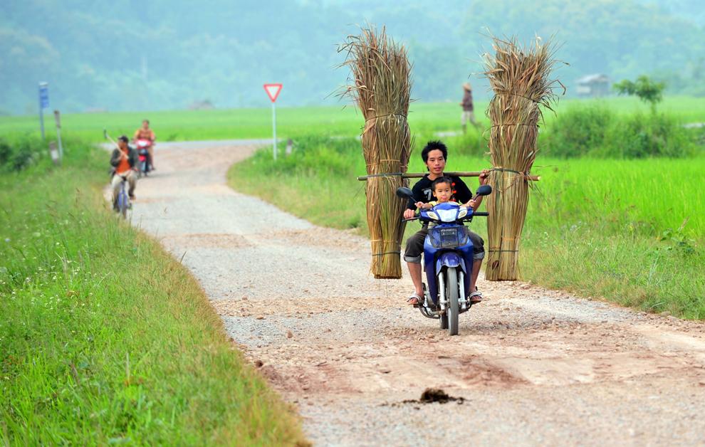 Un fermier şi fiul său merg cu motocicleta în Luang Namtha, în nordul Laosului, miercuri, 14 octombrie 2009.