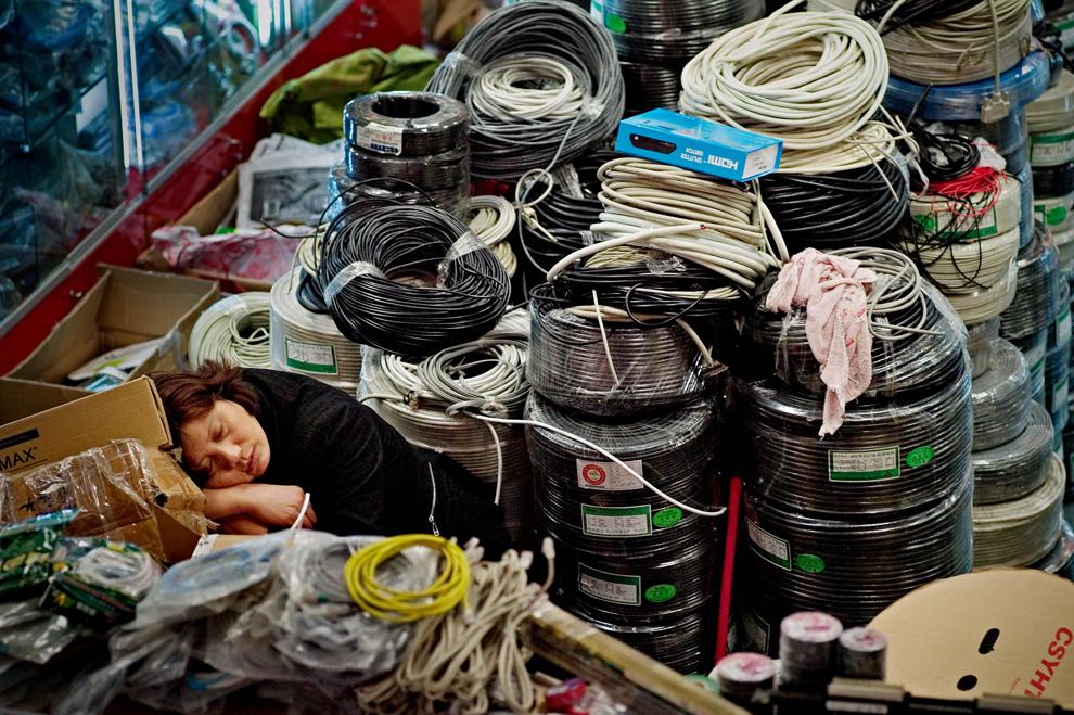 O femeie doarme printre cabluri expuse la vânzare într-un magazin de produse IT din Shanghai, vineri, 20 august 2010.