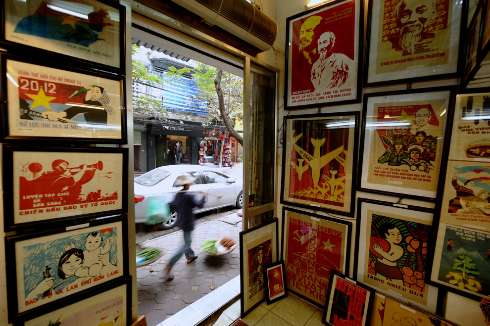 Un vânzător stradal trece pe lângă un magazin care comercializează postere cu propagandă de război, în Hanoi, marţi, 30 noiembrie 2010.