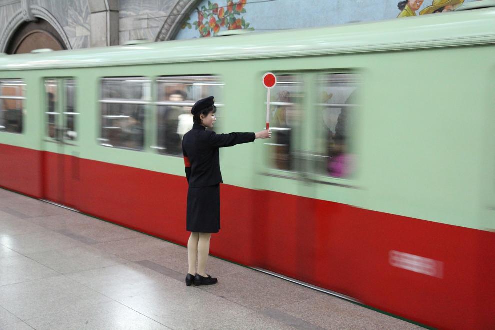 O femeie semnalizează în timp ce un tren pleacă dintr-o staţie de metrou a Phenianului, în Coreea de Nord, în aprilie 2011.