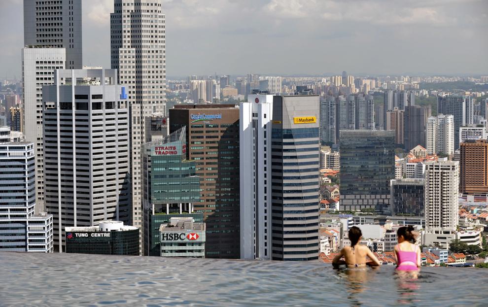 Oaspeţi ai hotelului Marina Bay Sands din Singapore privesc districtul financiar dintr-o piscină aflată pe acoperişul clădirii, luni, 13 mai 2013.