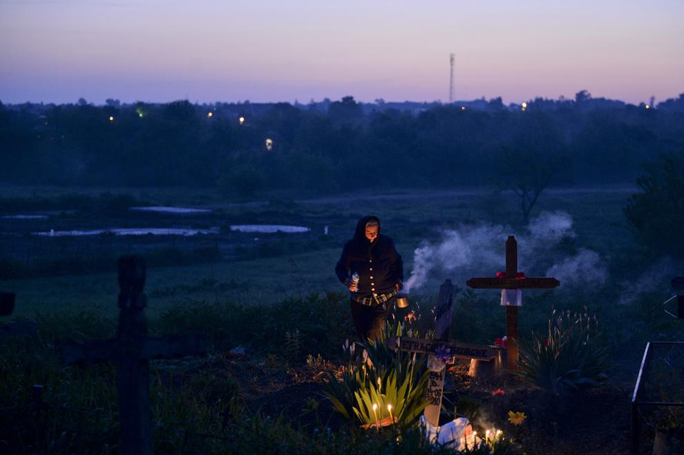 O femeie aprinde un foc în cimitirul din satul Copaciu, judeţul Giurgiu, joi, 2 mai 2013. În noaptea din Joia Mare din Săptămâna Patimilor locuitorii acestui sat îşi cinstesc rudele decedate aprinzând focuri la mormintele acestora şi oferind colaci si lumânări.
