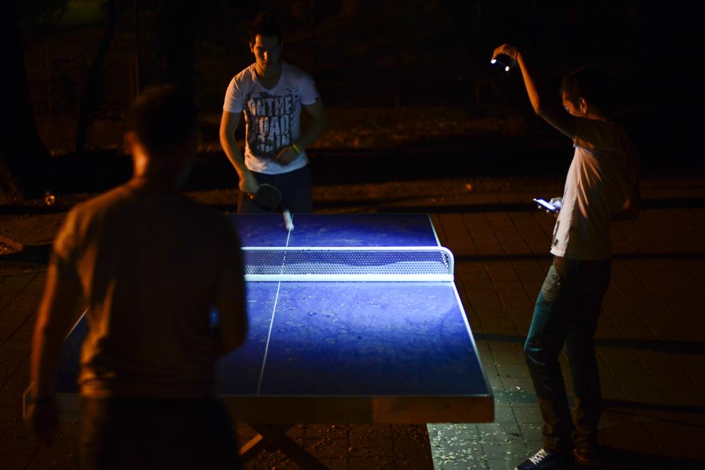 Doi tineri joacă tenis de masă în parcul Naţional (fost 23 August) la lumina unui telefon mobil, în Bucureşti, luni, 6 mai 2013.
