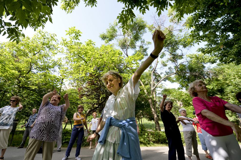 """O femeie face exerciţii în timpul programului de gimnastică în masă """"Bucura-te de primăvară, alege mişcarea în aer liber!"""", organizat de Primăria Sectorului 2 în Parcul Plumbuita din Bucureşti, luni, 20 mai 2013."""