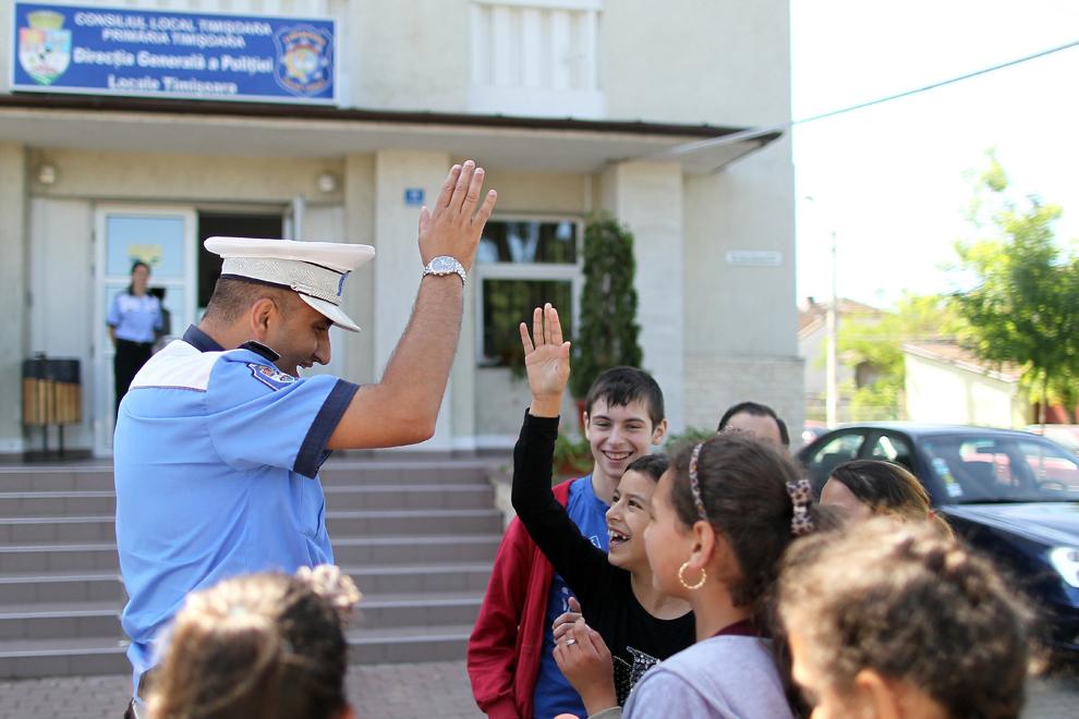Un poliţist se joacă cu un grup de copii cu ocazia Zilei Poliţiei Locale, la sediul Poliţiei din Timişoara, marţi, 21 mai 2013.