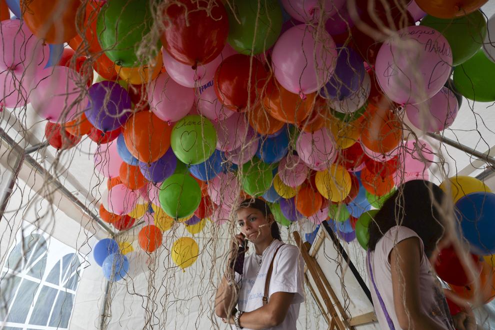 """O tânără vorbeşte la telefon înconjurată de baloane, în timpul celei de-a şasea ediţii a evenimentului """"Ziua Părinţilor de Îngeri"""" , organizat de Organizaţia E.M.M.A în parcul IOR din Bucureşti, duminică, 26 mai 2013."""