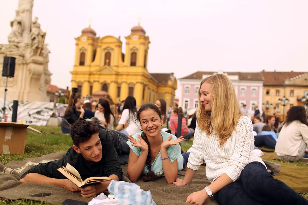 """Tineri stau pe iarba şi citesc în timpul concertului susţinut de Radu Stoica şi trupa Vest, în Piaţa Unirii din Timişoara, miercuri, 29 mai 2013, cu ocazia lansării de către Biblioteca Judeţeana Timiş a conceptului """"Pătura care citeşte"""" - picnic urban de lectura."""