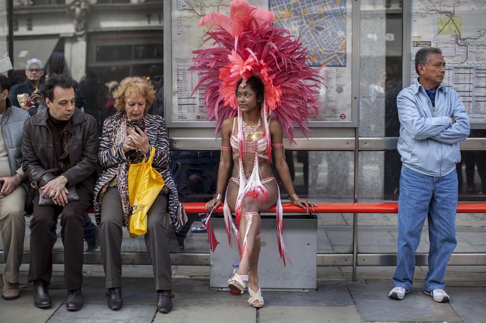 O dansatoare îmbrăcată în costumaţie de carnaval, reprezentând Trinidad Tobago, stă pe o bancă aflată într-o staţie de autobuz din Londra, în timpul evenimentul The World on Regent Street, duminică, 12 mai 2013.
