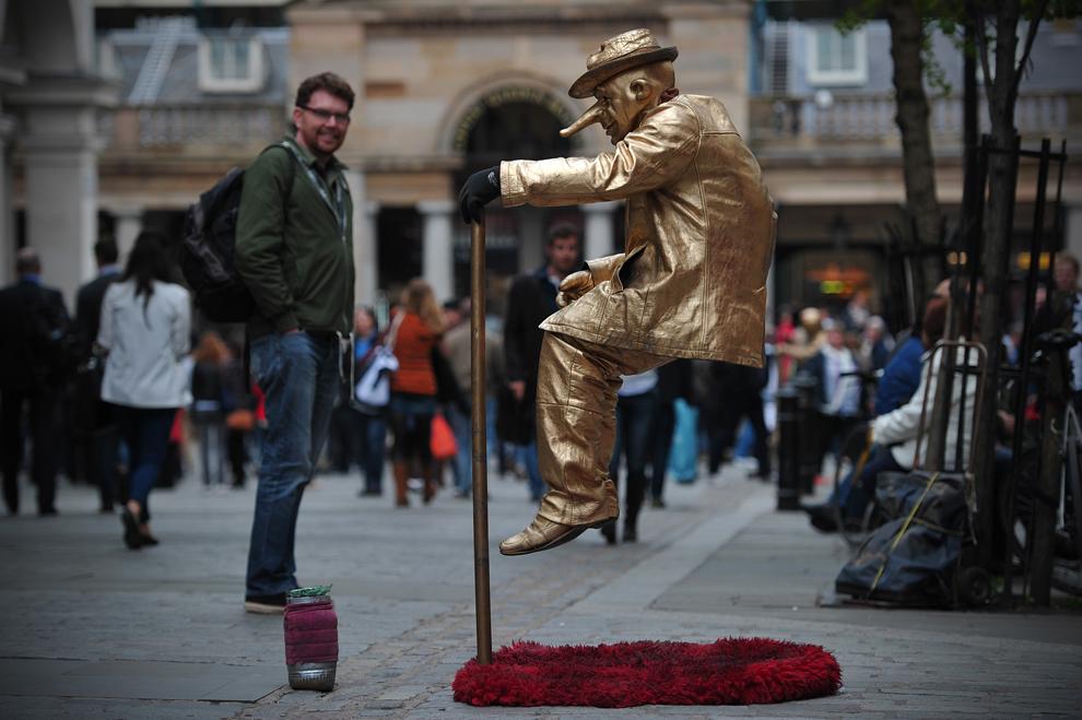 Un artist stradal poate fi văzut în districtul Covent Garden din Londra, vineri, 16 mai 2013.