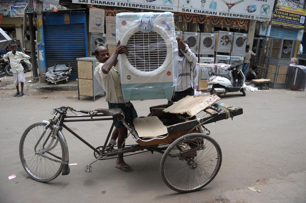 Un muncitor indian şi un client urcă un aparat de aer conditionat proaspăt achiziţionat  într-o ricşă, în Hyderabad, duminică, 19 mai 2013. Venirea verii face ca temperaturile înregistrate în câmpiile din nordul Indiei sa se situeze în jurul valorii de 48 de grade Celsius.