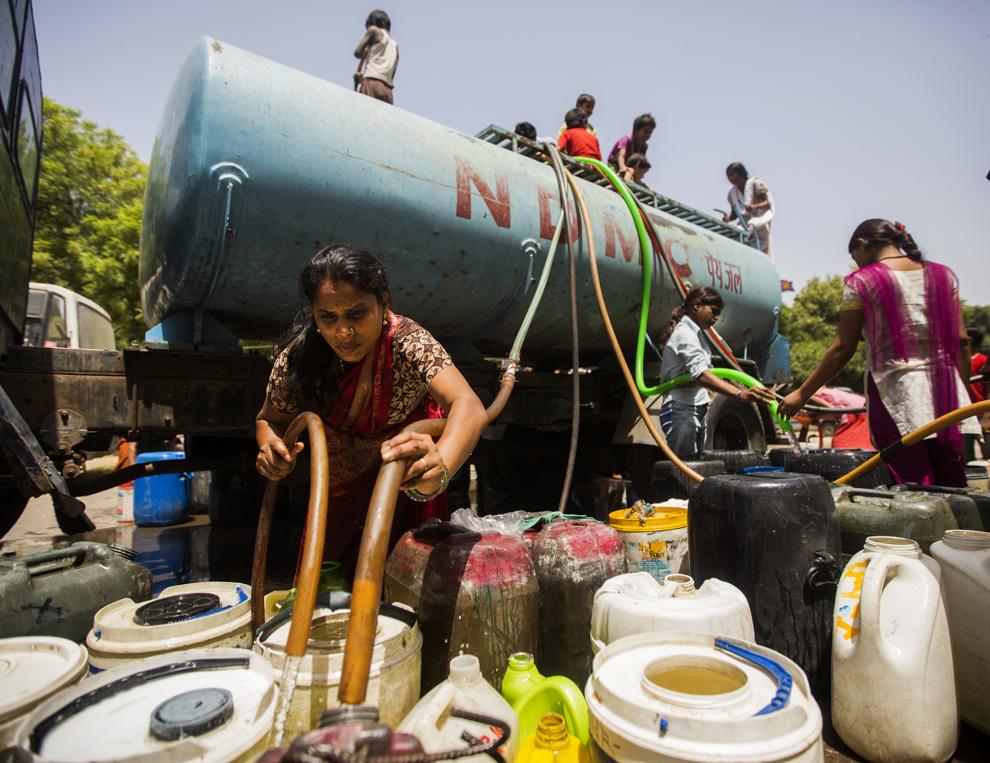 Rezidenţi indieni umplu mai multe containere cu apa adusă într-o cisternă de către autorităţi, în New Delhi, miercuri, 22 mai 2013.