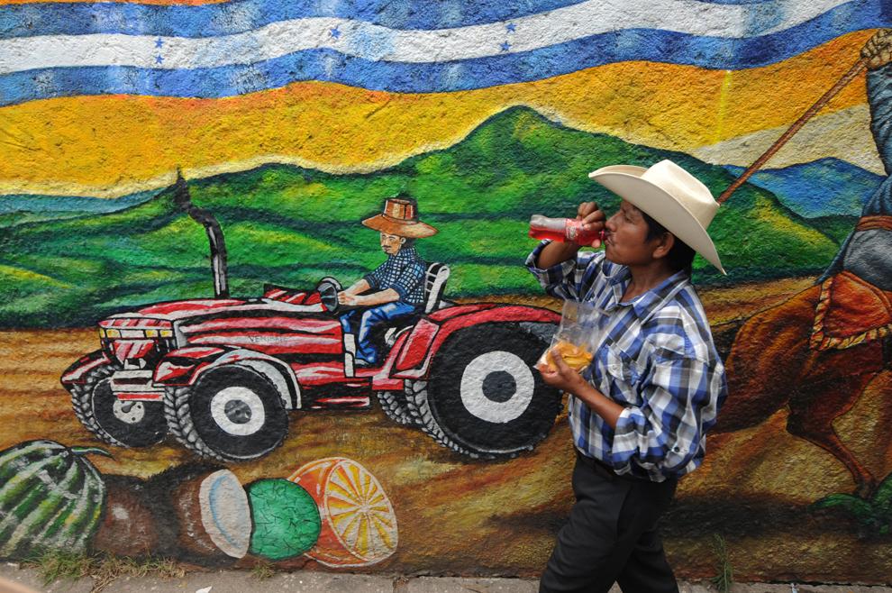 Un bărbat trece pe lângă o pictură murală din centrul oraşului Tegucigalpa din Honduras, joi, 23 mai 2013.