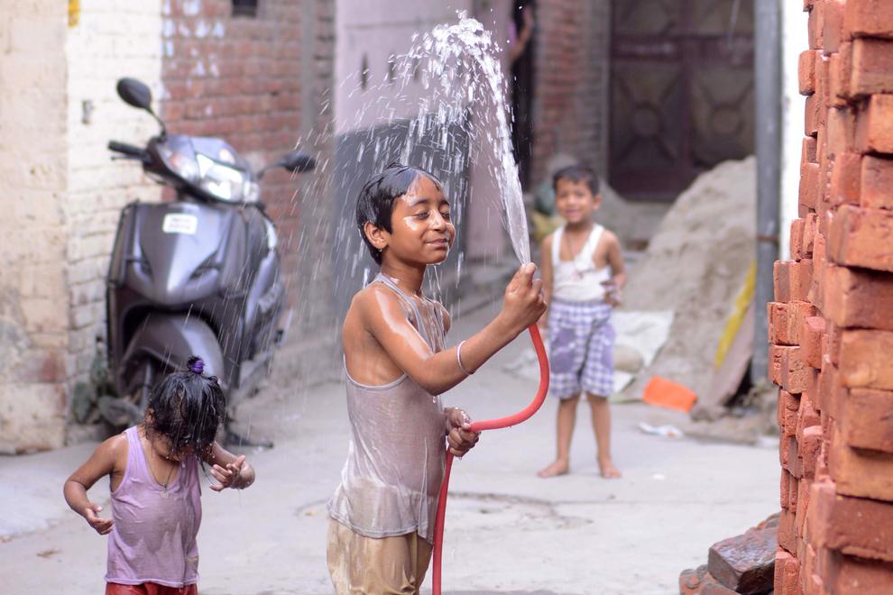 Un băiat indian se stropeşte cu apă pentru a se răcori, pe o stradă din Amritsar, marţi, 28 mai 2013. Venirea verii face ca temperaturile înregistrate în câmpiile din nordul Indiei sa se situeze în jurul valorii de 48 de grade Celsius.