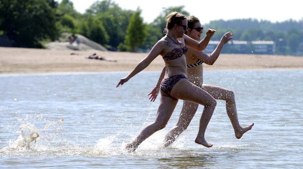 Senni Siltavouri (S) din Vantaa şi Sanna Vakkilainen din Espoo aleargă prin apă pe plaja Hietaniemi din Helsinki, vineri, 31 mai 2013. În timp ce marea parte a Europei suferă de pe urmă temperaturilor scăzute şi a ploii, finlandezii se bucură de temperaturi de peste 30 de grade Celsius.