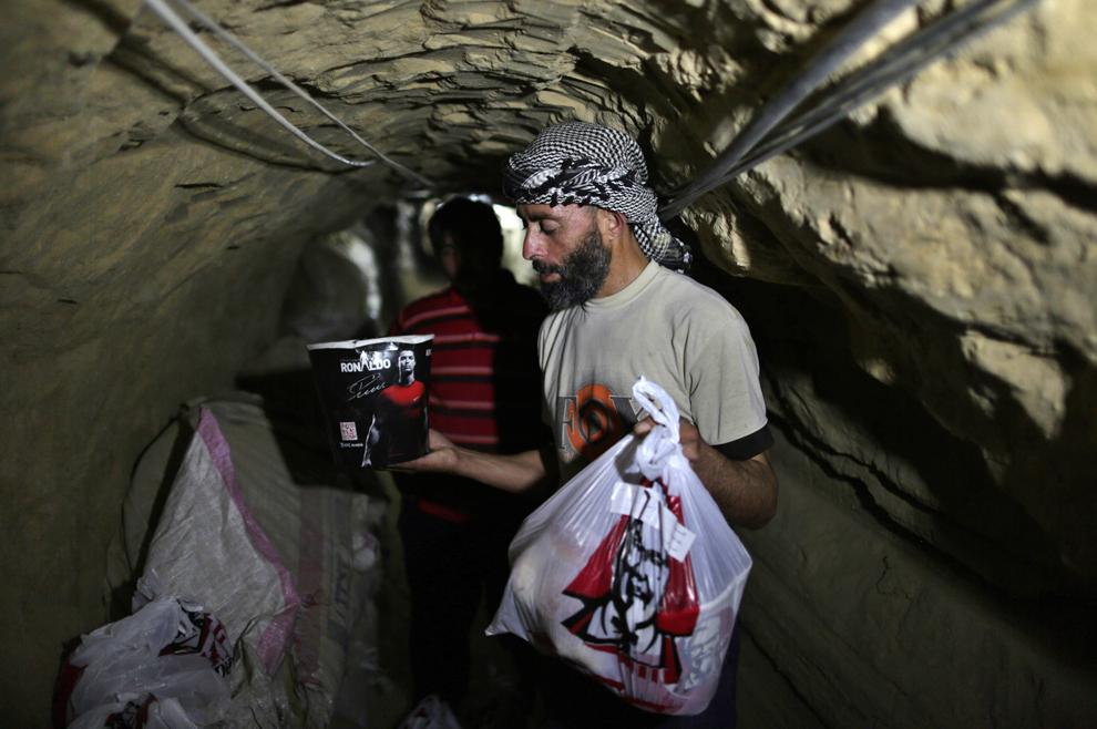 Un contrabandist livrează o pungă cu mâncare achiziţionată de la un restaurant KFC printr-un tunel subteran ce leagă Fâşia Gaza de Egipt, luni, 13 mai 2013. Mâncarea fast food reprezintă noua tendinţă pentru contrabandiştii care încearcă obţină profit introducând in Fâşia Gaza produse greu de găsit aici.