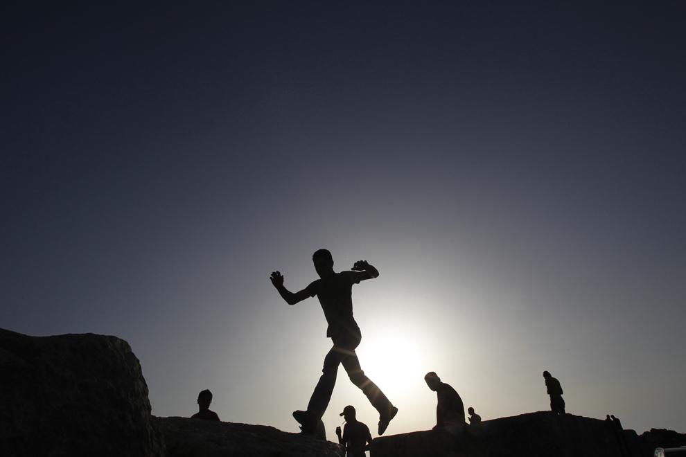 Trecători palestinieni urmăresc practicanţi de wakeboarding exersând în portul din Gaza City, vineri, 17 mai 2013.