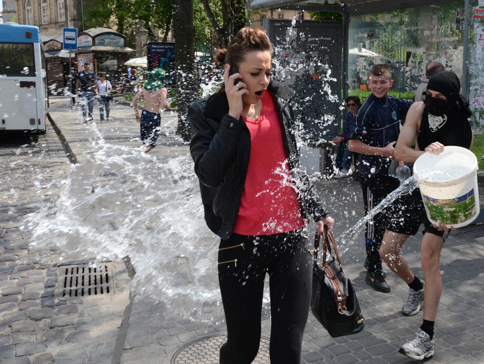 Mai mulţi tineri stropesc cu apă o femeie aflată în trecere cu ocazia sărbătorii Lunea Curată, cunoscută şi ca Lunea Udă, în prima zi de după Paştele Ortodox, în oraşul ucrainean Liov, luni, 6 mai 2013.