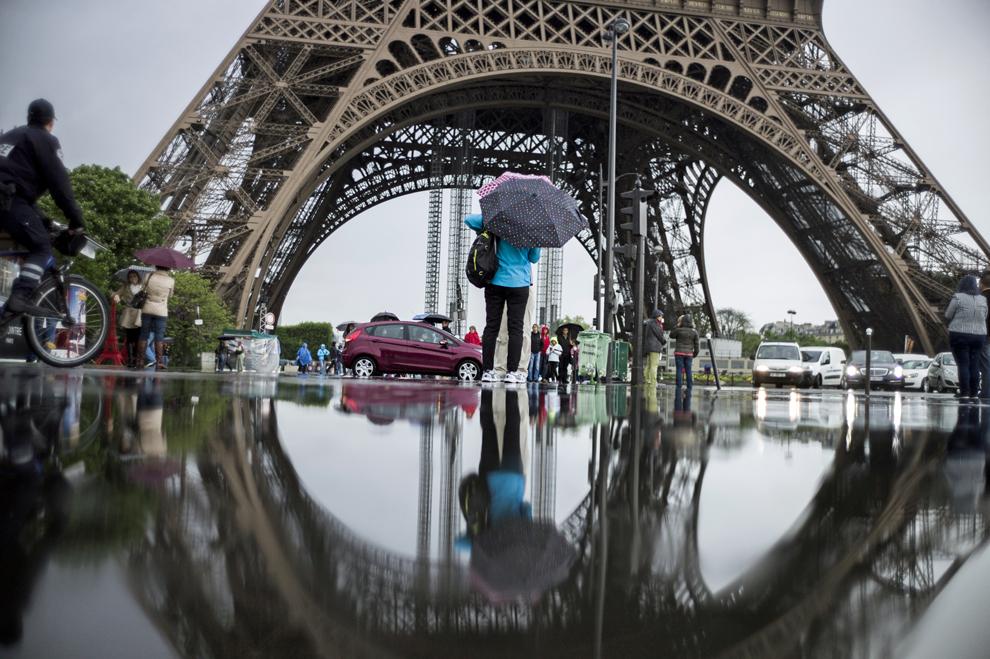 Turişti merg prin ploaie în apropierea turnului Eiffel din Paris, joi, 16 mai 2013.