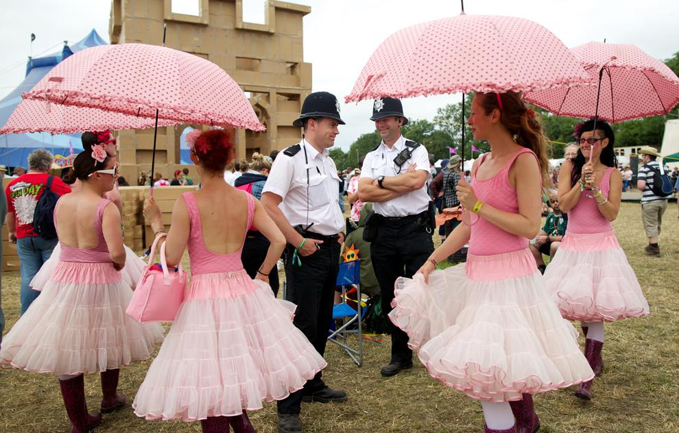 Actori îmbrăcaţi în costume de balerine înconjoară doi poliţişti, în cea de a cincea zi a Festivalului de la Glastonbury, duminică, 30 iunie 2013.