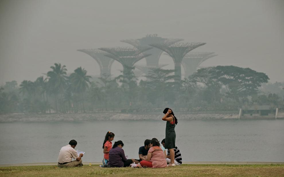 Oameni stau pe marginea unui golf din Singapore,  joi, 20 iunie, 2013.