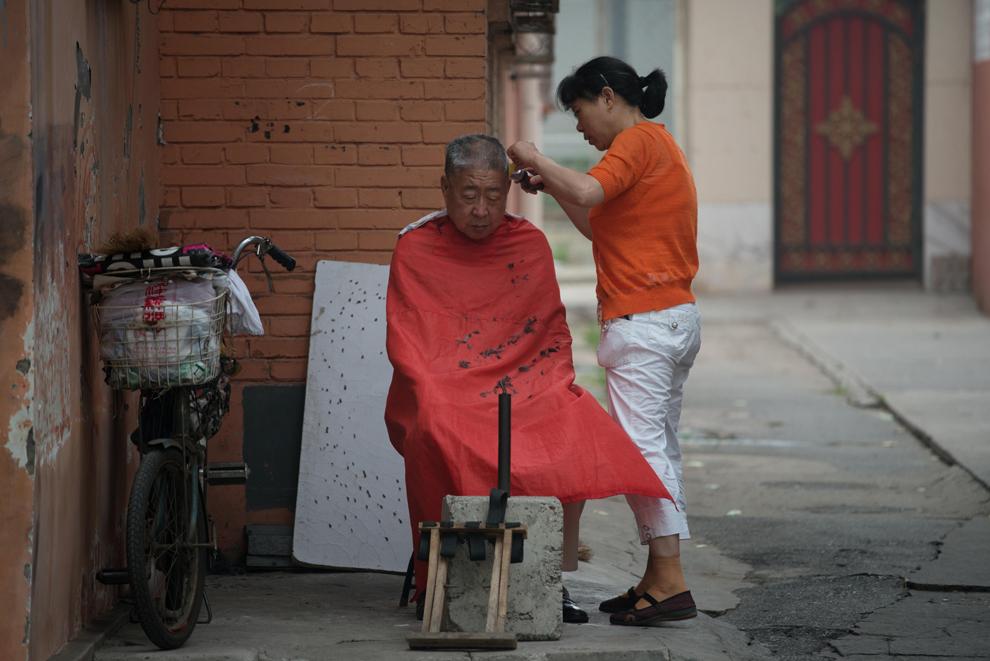 Un frizer tunde un client pe o alee din Beijing, vineri, 28 iunie, 2013.