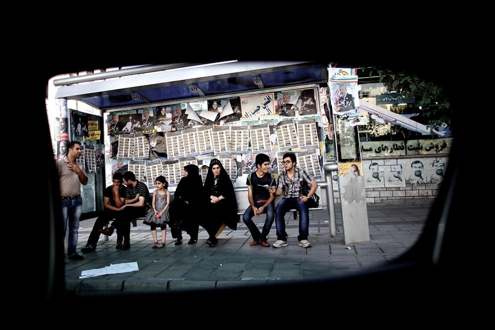 O fotografie făcută din interiorul unui autovehicul arată iranieni aşteptând într-o staţie de autobuz, în Teheran, Iran, joi, 13 iunie 2013.