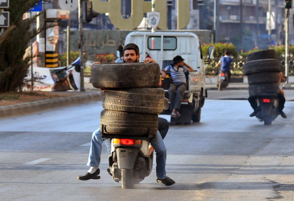 Bărbaţi transportă cauciucuri cu scuterul către o baricadă in flăcări din nordul orasului Tripoli, duminică, 23 iunie 2013.