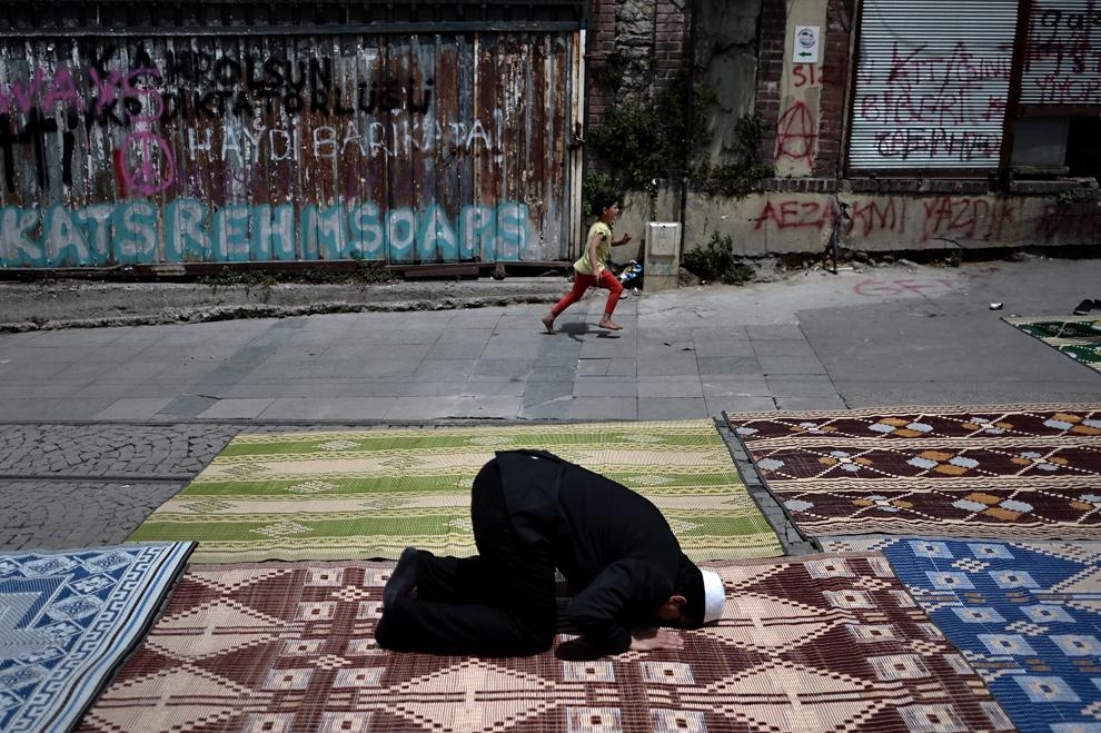 Un băiat fuge pe lângă un bărbat care îşi face rugaciunea lângă piaţa Taksim, în Istanbul, vineri, 7 iunie 2013.