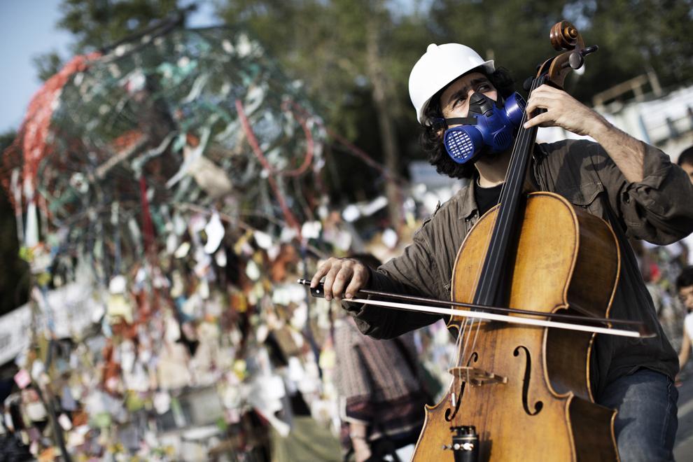 Un bărbat purtând o cască de protecţie şi o mască de gaze cântă la violoncel în Piaţa Taksim, sâmbătă, 15 iunie 2013.