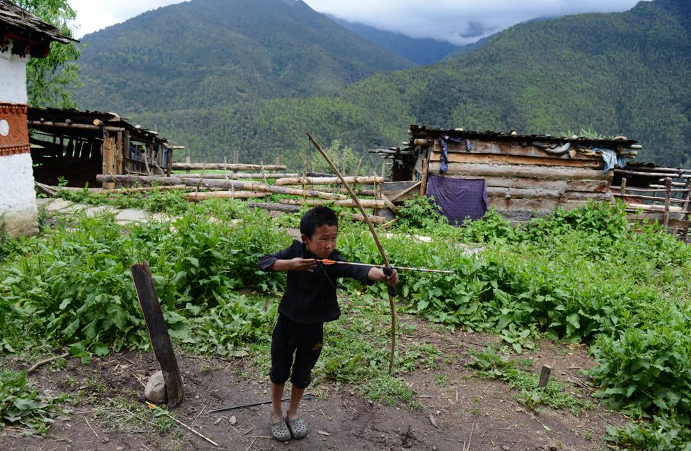 Un copil din Bhutan ţinteşte cu săgeata în faţa casei sale din zona oraşului Paro, duminică, 2 iunie 2013.