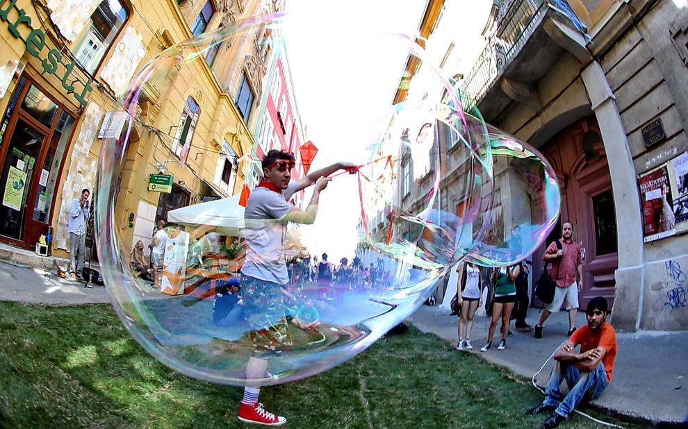 Un tânăr artist realizează baloane de săpun uriaşe, în cadrul festivalului Street Delivery care se desfăşoară timp de trei zile la Timişoara, pe strada Mercy, sâmbată, 15 iunie 2013.