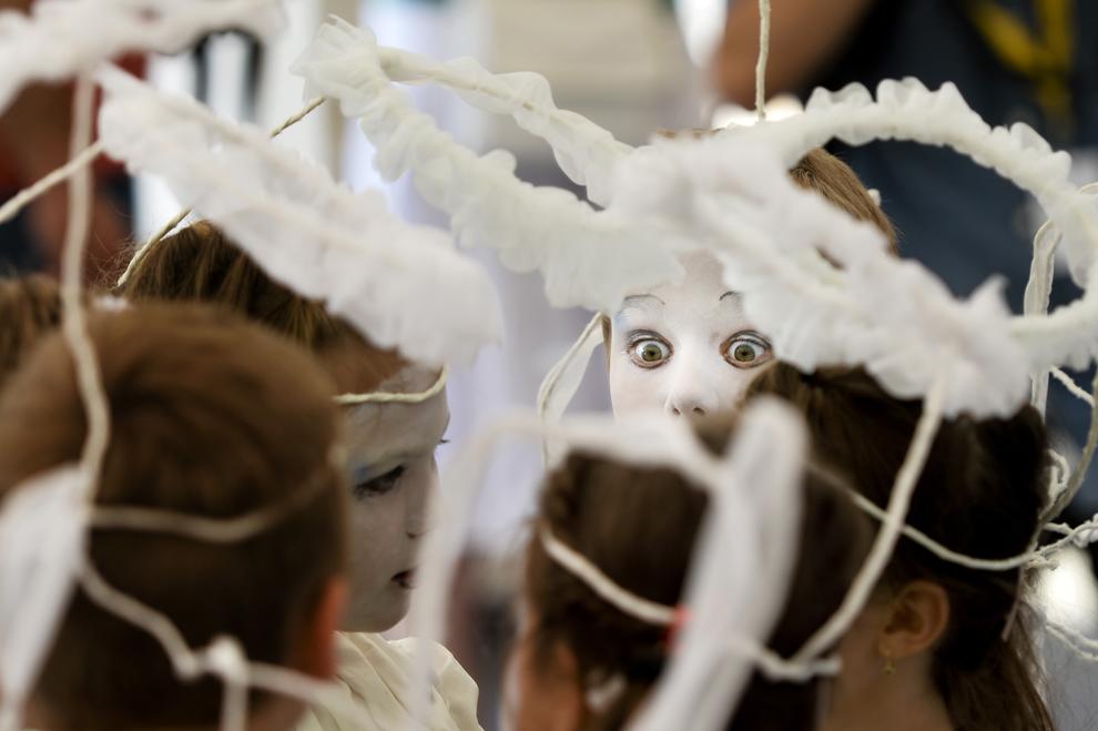 """Un băieţel îmbrăcat în îngeraş, se priveşte în oglindă în timpul pregătirilor pentru piesa """"Îngeraşii"""", din cadrul celei de-a III-a ediţii a Festivalului internaţional de statui vivante, desfăşurat în Parcul Herăstrău din Bucureşti, vineri, 21 iunie 2013."""