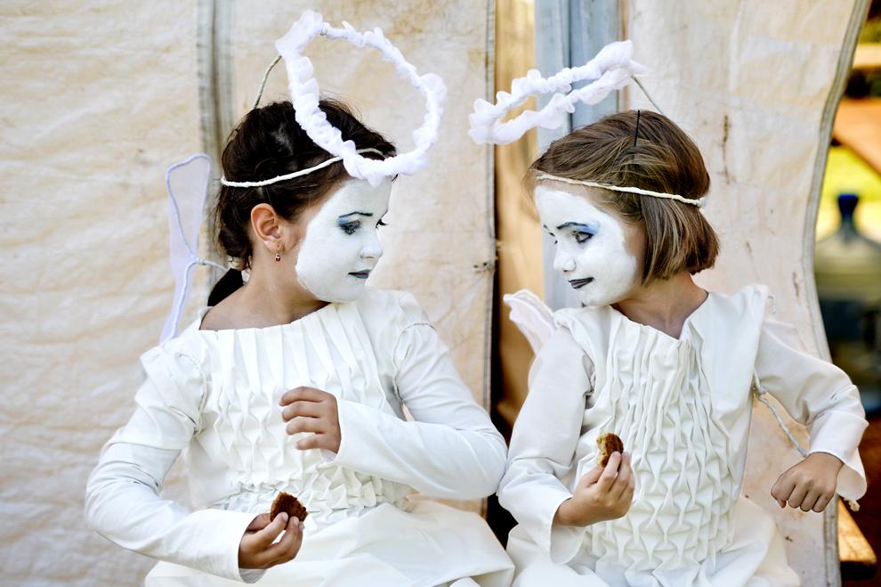 """Doua fetiţe îmbrăcate în îngeraşi se relaxează în timpul pregătirilor pentru piesa """"Îngeraşii"""" din cadrul celei de-a III-a ediţii a Festivalului internaţional de statui vivante, în Bucureşti, vineri, 21 iunie 2013."""