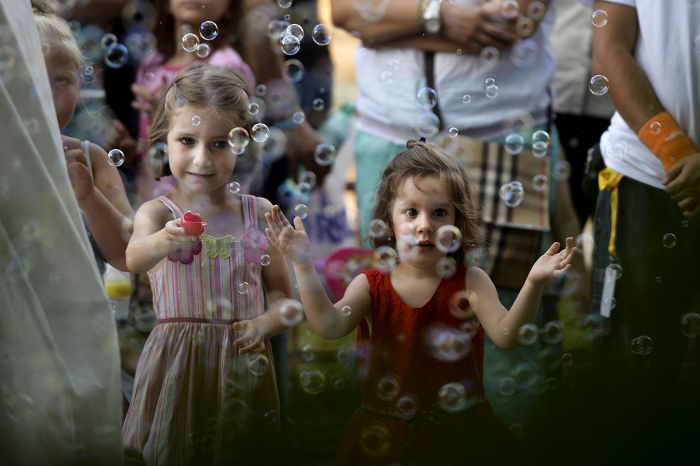 Doua fetiţe se joacă cu baloane de săpun în timpul unei piese de teatru, în cadrul celei de-a III-a ediţii a Festivalului internaţional de statui vivante, desfăşurat în Parcul Herăstrău din Bucureşti, vineri, 21 iunie 2013.