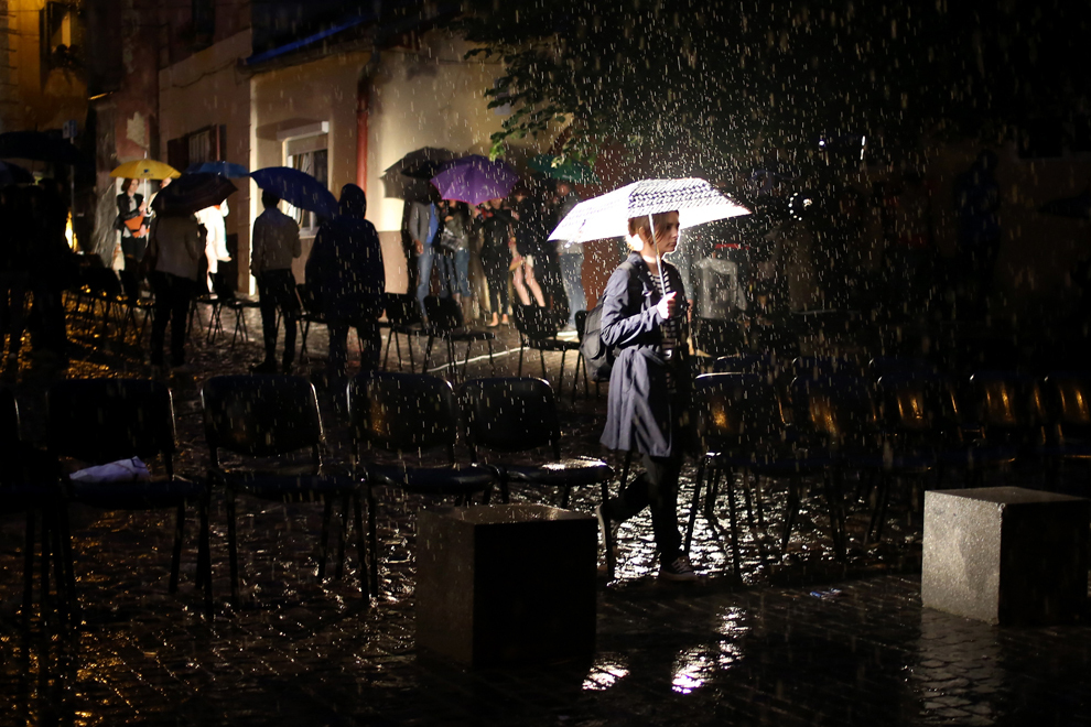 Persoane cu umbrele în mâini merg prin ploaie, pe o stradă din Sibiu, joi, 28 iunie 2013.