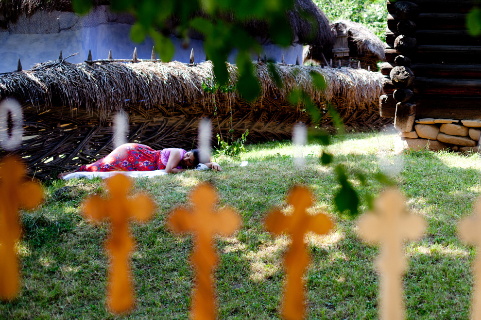"""O femeie se odihneşte pe iarbă, în Muzeul National al Satului """"Dimitrie Gusti"""", Bucureşti, 29 iunie 2013."""
