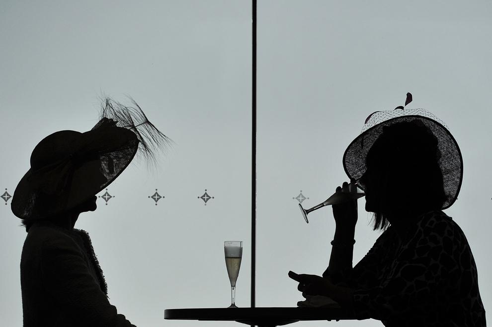 Două femei beau şampanie în timpul celei de-a patra zi a festivalului de curse de cai Royal Ascot din Berkshire, Ascot, la vest de Londra, vineri, 21 iunie 2013.